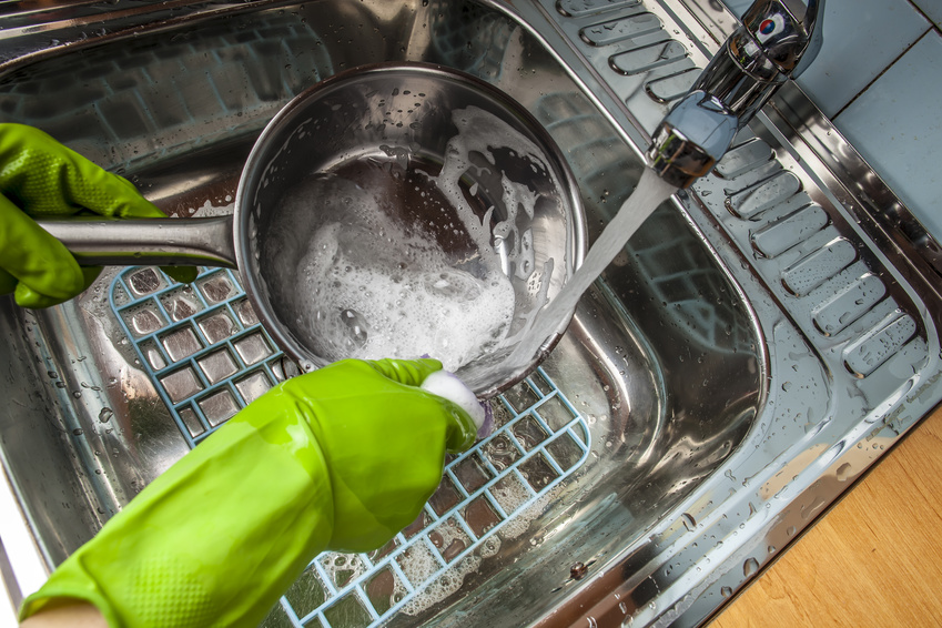 man washing dishes in the sink