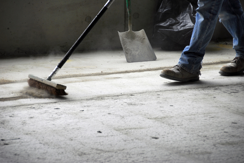 The legs and feet of a construction worker sweeping up on rough concrete at a job site using a large broom